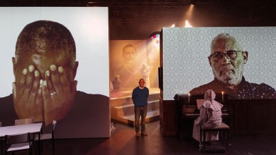 "Israel Kaunatjike (Mitte), Talita Uinuses und Israel Kaunatjike (Video) in ""Herero_Nama - A History of Violence"" von Nuran David Calis am Schauspiel Köln. (David Baltzer)"