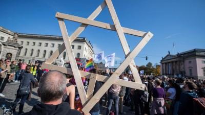 Ein Mann auf der Berliner Unteilbar-Demonstration trägt einen riesigen hölzernen Davidstern durch die Menge. (Imago / epd / Christian Ditsch)