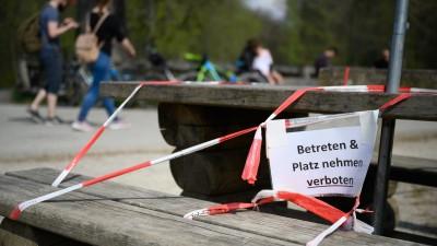 """Ein Schild mit der Aufschrift """"Betreten & Platz nehmen verboten"""" hängt am 13.04.2020 am Bärenschlössle, einem beliebten Ausflugsziel in Stuttgart, an einer Bank. (dpa / picture alliance / Sebastian Gollnow)"""