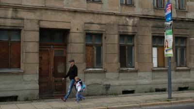 Ein Mann mit seinem Kind passiert ein Gebäude in desolatem Zustand im Mai 2019 in der ostdeutschen Grenzstadt Görlitz. (Getty Images / Sean Gallup)