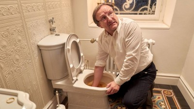 Szenefoto aus dem Fernsehfilm. Josef Asch, gespiel von Rainer Bock greift in einem Badezimmer mit der rechten Hand in die Toilettenschüssel.  (WDR/Frank Dicks)