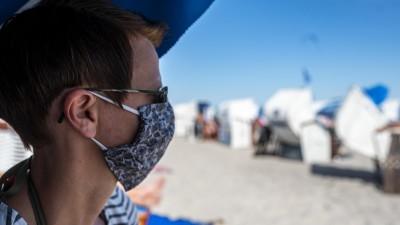 Gesellschaft: Urlaub, Ostsee. Eine Frau trägt eine Mund-Nasen-Maske am Strand von Grömitz. Das Bundesland Schleswig-Holstein empfängt in der Corona-Pandemie die ersten Urlauber. | Verwendung weltweit (picture alliance / David Inderlied/Kirchner-Media)
