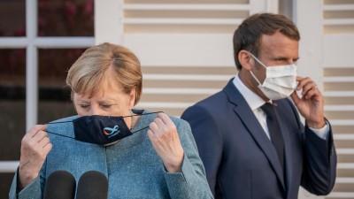 Emmanuel Macron, Präsident von Frankreich, kommt hinter Bundeskanzlerin Angela Merkel (CDU), zur Pressekonferenz in der Sommerresidenz des Staatschefs, dem Fort de Bregancon. Die frühere Festung liegt auf einem Felsen an der Mittelmeerküste in der Nähe von Toulon. (picture alliance / dpa / Michael Kappeler)