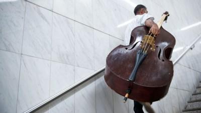 Ein Mann sitzt auf einer Trommel, vor ihm steht ein offener Gitarrenkoffer. (picture alliance / dpa / Foto: Emily Wabitsch)