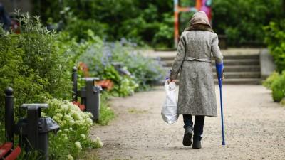 Rückansicht einer Rentnerin mit Krücke, die durch einen Park geht und dabei eine Plastiktüte mit Pfandflaschen trägt. (imago images / Schöning)