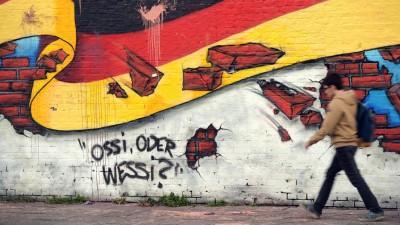"""Ein Passant gehtan einem Wandbild mit der deutschen Nationalflagge und dem Schriftzug """"Ossi oder Wessi?"""" vorbei. (dpa/ Rainer Jensen)"""