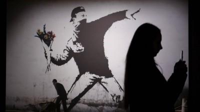 """Das Bild zeigt die Schatten von Besuchern einer Banksy-Ausstellung in St. Petersburg, Russland. Zu sehen ist das Bild """"The Flower Thrower"""" - der Blumenwerfer, das stilisierte Abbild eines Protestierenden, der mit seinem Arm weit ausholt, um einen Strauß Blumen zu werfen. (imago/ITAR-TASS)"""