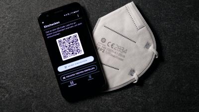 Auf einem Smartphone wird die Check-In-app Luca angezeigt, daneben liegt ein FFP2- Mundschutz (Imago Images / Futureimages)