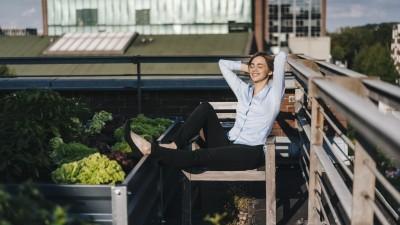 Eine Frau in Hemd und Geschäftshose hat auf einem Dachgarten die Beine hochgelegt und entspannt in der Sonne. (Getty Images / Westend61)