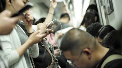 Fahrgäste in der U-Bahn der chinesischen Hauptstadt Peking benutzen am 3.7.2015 ihre Smartphones. (picture-alliance / dpa / Liu Zhuoqun)