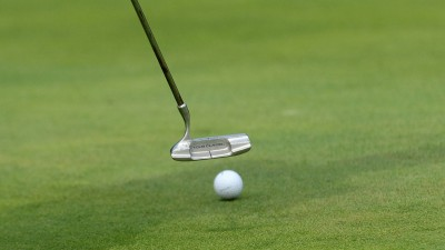 Golfschläger und Ball auf grünem Rasen (imago / Schwörer)