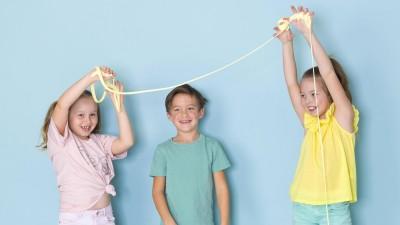 Kinder spielen vor hellblauem Hintergrund mit Schleim. (imago images / Hannes Eichinger)