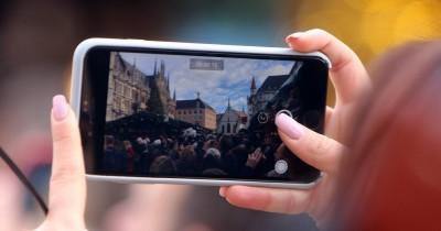 Besucherin filmt mit ihrem Smartphone den Christkindlmarkt auf dem Marienplatz am Rathaus in München, Bayern, Deutschland (imago /Marcel Lorzen)