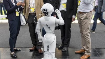 Auf der Messe CEBIT steht ein SoftBank Roboter in einer Gruppe von Menschen.  (picture alliance/ Jochen Tack)