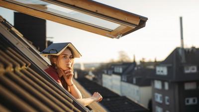 Eine junge Frau schaut nachdenklich aus einem Dachfenster mit einem aufgeschlagenen Buch über dem Kopf. (Getty Images / Westend61)