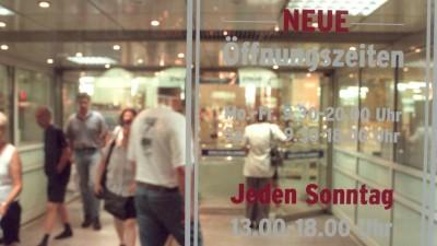 """Eingangstür zu einem Kaufhaus mit der Aufschrrift """"Neue Öffnungszeiten - Jeden Sonntag 13.00 - 18.00 Uhr"""" (dpa/Peter Endig)"""