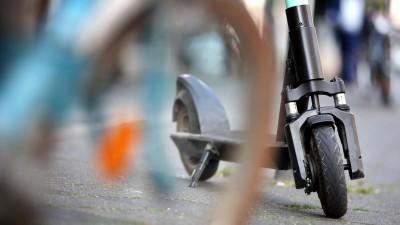 """Ein E-Tretroller der Verleihfirma """"Tier"""" steht in der Innenstadt hinter einem abgestellten Fahrrad. (picture alliance / dpa / Martin Gerten)"""