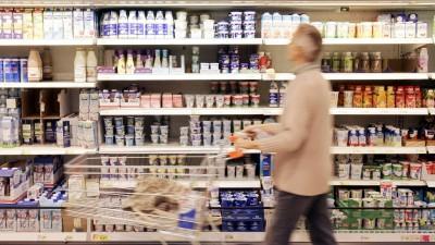 Ein Supermarktregal mit Plastikverpackungen. Davor geht ein grauhaariger Mann mit einem Einkaufswagen. (picture alliance / Keystone / Jochen Zick)