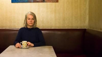 Eine Frau mit grauen Haaren sitzt in einem Café, hinter ihr an der Wand ist ein Gemälde. Sie hält in ihren Händen eine weiße Tasse. (Picture Alliance / dpa / picturedesk.com / Wolfgang Paterno)