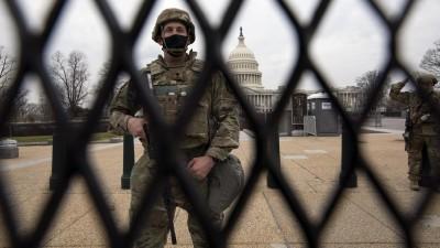 Durch einen Zaun hindurch ist ein Soldat zu sehen, der ein Gewehr vor sich hält. Im Hintergrund kann man das US-Kapitol in Washington mit seiner markanten weißen Kuppel sehen. (FR159526 AP)