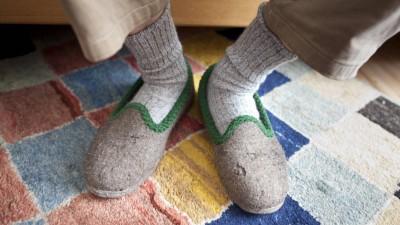 Ein Rentner steckt seine Füße in seine Filzpantoffeln. (imago/ Ute Grabowsky)