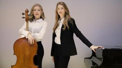 Zwei junge Frauen stehen nebeneinander und schauen in die Kamera. Die linke hält ihr Cello vor sich, die rechte hat ihre Hand auf einem geschlossenen Flügel abgelegt. (Felix Broede)