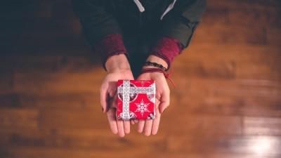 Ein kleines Geschenk in weihnachtlicher Verpackung wird auf zwei Händen überreicht. (unsplash / Ben White)