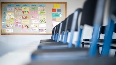 Nordrhein-Westfalen, Übach-Palenberg: Stühle stehen in einem leeren Klassenzimmer auf den Tischen, während im Hintergrund ein Stundenplan zu sehen ist. (dpa-Bildfunk / Jonas Güttler)