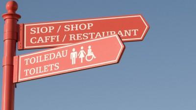 Zweisprachiger Wegweiser auf Englisch und Walisisch zuRestaurant, Laden und Toiletten in Wales (Imago)