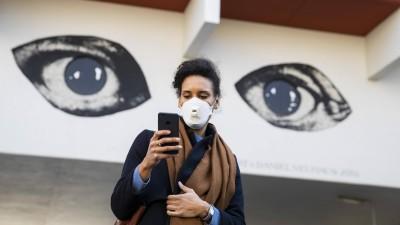 Eine Junge Frau schaut auf ihr Handy mit den Augen eines Grafitti im Hintergrund. (imago-images / Emmanuele Contini)