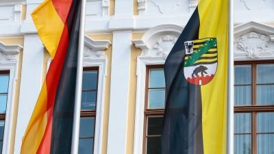 Deutschland- und Landesfahne von Sachsen-Anhalt vor der gelb-weißen Fassades des Landtags von Sachsen-Anhalt am Domplatz in Magdeburg. (Imago / Jan Huebner)