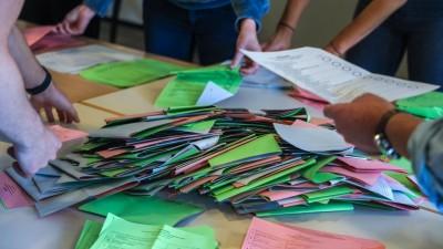 Viele Wahlzettel liegen in Stapeln auf einem Tisch, vier Menschensortieren sie. (imago / Rüdiger Wölk)