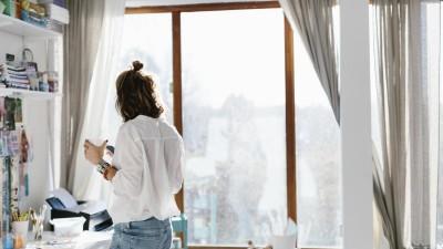 Eine Frau steht mit ihrem Smartphone und einer Tasse Kaffee in der Hand in ihrem Home Office. (Eyeem / Johnér Agency)