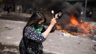 Proteste in Chile gegen Preiserhöhungen im öffentlichen Nahverkehr. Eine Frau schlägt auf ein Gefäß, im Hintergrund brennender Müll auf der Straße. (picture alliance / AA / Cristobal Venegas)