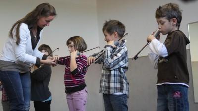 Eine Frau hilft vier Kindern beim Stimmen ihrer Geigen. (Picture Alliance / dpa / Johannes Reichert)