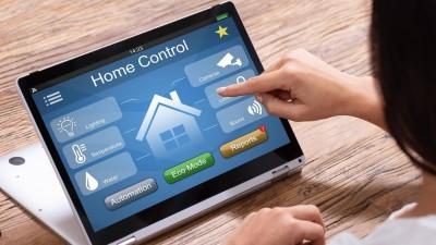 Frau bedient an einem Tablet ein Smart Home Control System für z.B.  Licht, Temperatur, Wasser, Überwachung (Andrey Popov / Panthermedia / imago-images)