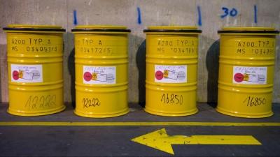 Vier gelbe Fässer mit radioaktivem Abfall stehen neben einem Weg auf dem ein gelber Richtungspfeil am Boden nach rechts zeigt. (picture alliance / dpa / Wolfram Kastl)