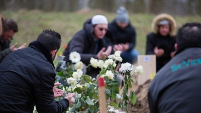 Männer sitzen um ein Grab und beten mit erhobenen, zum Himmel geöffneten Handflächen. (picture alliance / Christoph Soeder/dpa | Christoph Soeder)