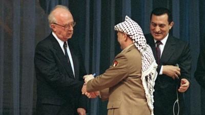 PLO-Chef Jassir Arafat und Israels MinisterpräsidentJitzchak Rabinreichen sich nach der Unterzeichnung desGaza-Jericho-Abkommens am 4. Mai 1994 (PATRICK BAZ / AFP)