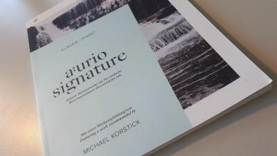 """Auf einer Tischplatte liegt ein helles Magazin, auf dem """"aurio signature"""" steht. (Deutschlandradio/Jonas Zerweck)"""