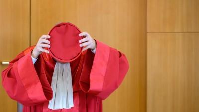 AndreasVoßkuhle, Vorsitzender des Zweiten Senats beim Bundesverfassungsgericht, setzt nach der Urteilsverkündung des zweiten Senats des Bundesverfassungsgerichts (BVerfG) zu milliardenschweren Staatsanleihenkäufen der Europäischen Zentralbank (EZB) am 05.05.2020 seine Kopfbedeckung auf. (dpa / Sebastian Gollnow)