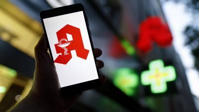 Das Apotheken-Logo erscheint auf einem Smartphone. Im Hintergrund ist eine Apotheke zu erkennen. (imago/ Future Image/C. Hardt)