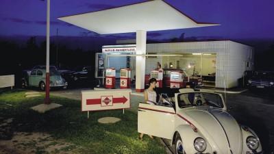 Vor einer Tankstelle steht ein beigebrauner Käfer Cabrio, auf der Beifahrerseite steigt gerade eine junge Frau ein. Aufnahme von 1958. (akg-images / Dodenhoff)