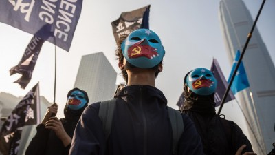 Schwarzgekleidete Demonstranten tragen blaue Gesichtsmasken. Darauf gemalt sind Hände mit einer chinesischen Flagge in Form einer Hand, die den Mund zuhält. (AFP/Dale de la Rey)