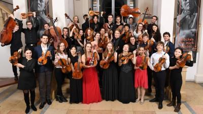 Die Preisträger des Deutschen Musikinstrumentenfonds 2018 haben sich zu einem Gruppenbild versammelt und strecken ihre Streichinstrumente in die Höhe. (David Ausserhofer)