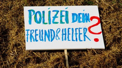 """""""Polizei dein Freund und Helfer?"""", steht geschrieben auf einem Schild in blauen Buchstaben und mit rotem Fragenzeichen auf einer grünen Wiese liegend. (picture alliance / chromorange / Martin Schroeder)"""