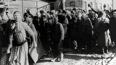 Überlebende des Konzentrationslagers Auschwitz verlassen das Lager und machen dabei Siegesgesten. (imago/Reinhard Schultz)