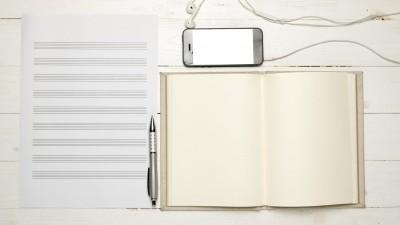 Leeres Notenpapier liegt auf einem hellen Holztisch. Daneben liegen ein Kugelschreiben, ein leeres Notizbuch und ein Smartphone mit Kopfhörern. (imago images / agefotostock)