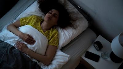 Eine Frau liegt in einem Bett und schläft (picture alliance / dpa / Christin Klose)