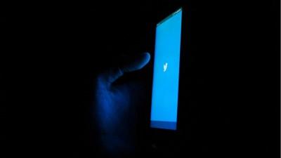 Eine Hand hält ein Smartphone mit blauem Twitterlogo auf dem Display in der Dunkelheit. (unsplash/Akshar Dave)